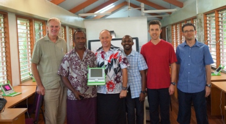 Team members with Ian from the University of the South Pacific and Chief Jone displaying the new laptop
