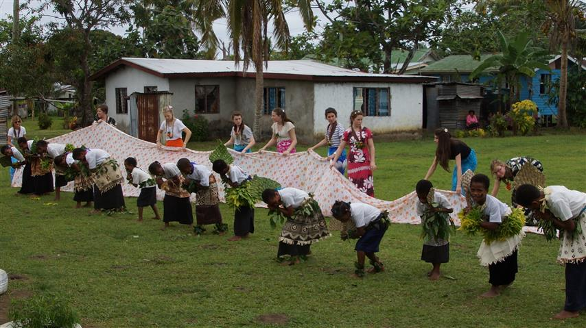 The girls lay down some cloth during the dance as a gift and  cultural response of thanks
